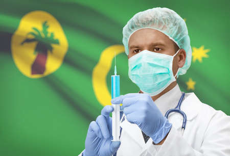 cocos: Doctor with syringe in hands and flag on background - Cocos (Keeling) Islands