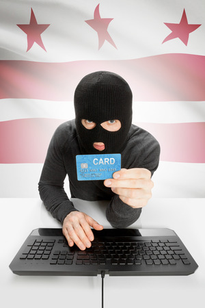 columbia district: Hacker in black mask with USA state flag on background - District of Columbia