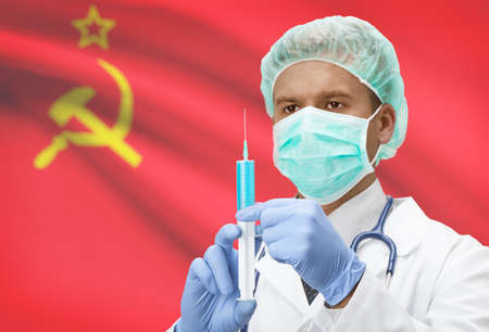 soviet flag: Doctor with syringe in hands and flag on background - USSR - Soviet Union