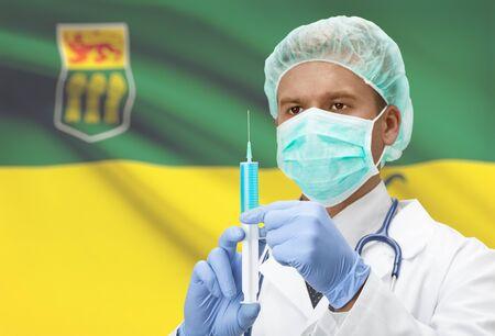saskatchewan flag: Doctor with syringe in hands and Canadian province flag on background - Saskatchewan