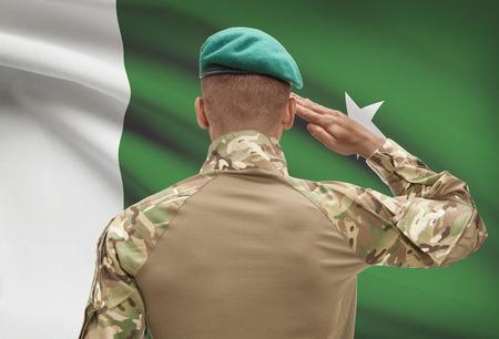 Dark-skinned soldier in hat facing national flag series - Pakistan