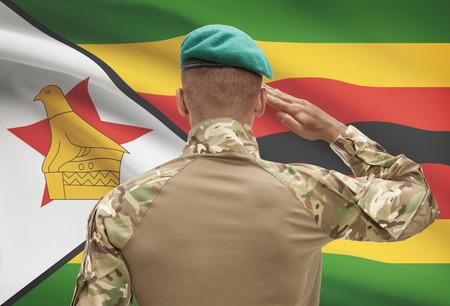Dark-skinned soldier in hat facing national flag series - Zimbabwe