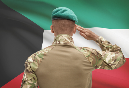 Dark-skinned soldier in hat facing national flag series - Kuwait