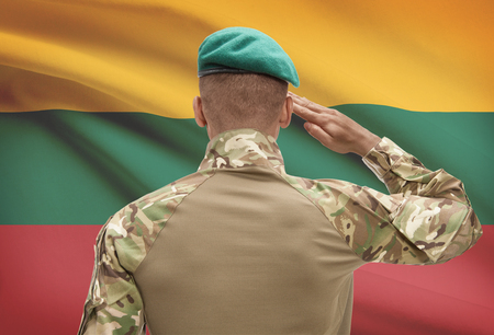Dark-skinned soldier in hat facing national flag series - Lithuania