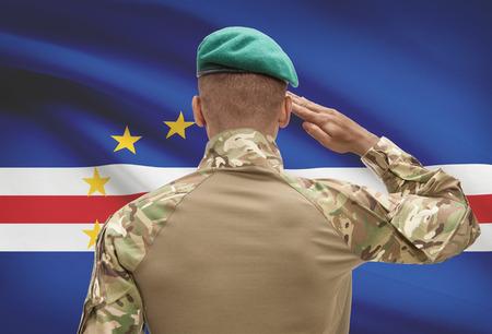 Dark-skinned soldier in hat facing national flag series - Cape Verde
