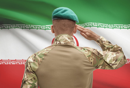 Dark-skinned soldier in hat facing national flag series - Iran Stock Photo