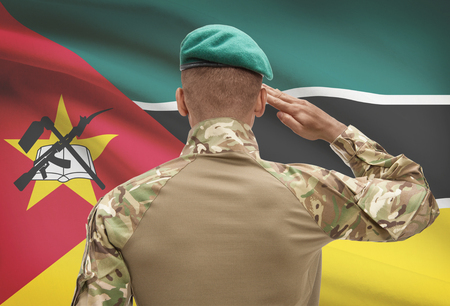 troop: Dark-skinned soldier in hat facing national flag series - Mozambique