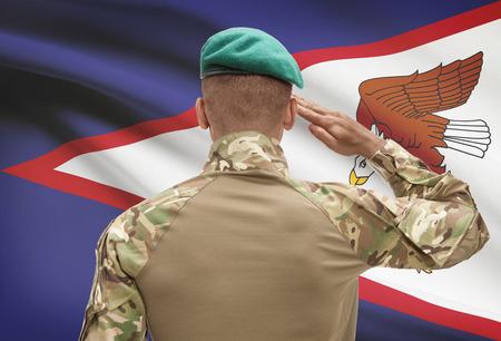 Dark-skinned soldier in hat facing national flag series - American Samoa Stock Photo