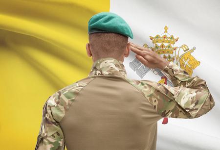 Dark-skinned soldier in hat facing national flag series - Vatican City