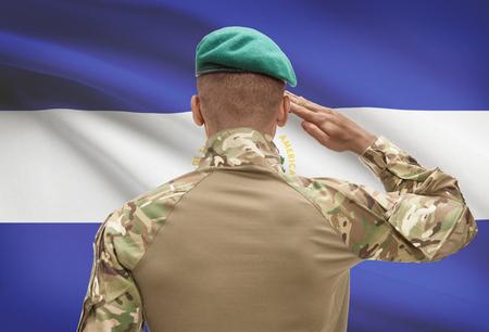 Dark-skinned soldier in hat facing national flag series - El Salvador
