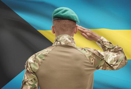 Dark-skinned soldier in hat facing national flag series - Bahamas