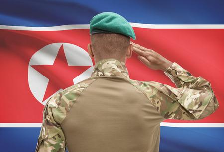 Dark-skinned soldier in hat facing national flag series - North Korea Stock Photo
