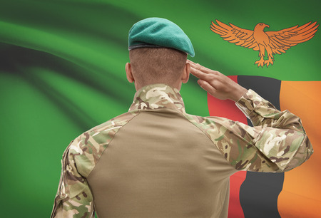 Dark-skinned soldier in hat facing national flag series - Zambia