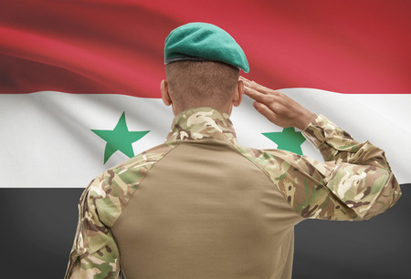 Dark-skinned soldier in hat facing national flag series - Syria