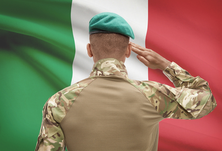 Dark-skinned soldier in hat facing national flag series - Italy Stock Photo