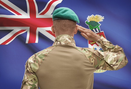 cayman islands: Dark-skinned soldier in hat facing national flag series - Cayman Islands Stock Photo