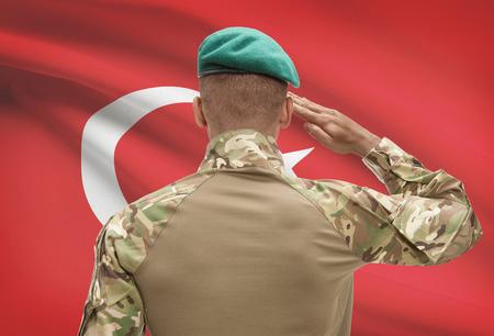 troop: Dark-skinned soldier in hat facing national flag series - Turkey