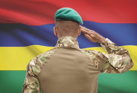 Dark-skinned soldier in hat facing national flag series - Mauritius Stock Photo