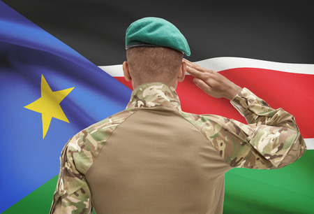 Dark-skinned soldier in hat facing national flag series - South Sudan Stock Photo