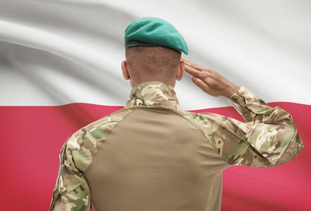 Dark-skinned soldier in hat facing national flag series - Poland