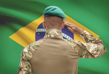 Dark-skinned soldier in hat facing national flag series - Brazil Stock Photo