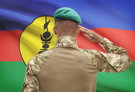 new caledonia: Dark-skinned soldier in hat facing national flag series - New Caledonia