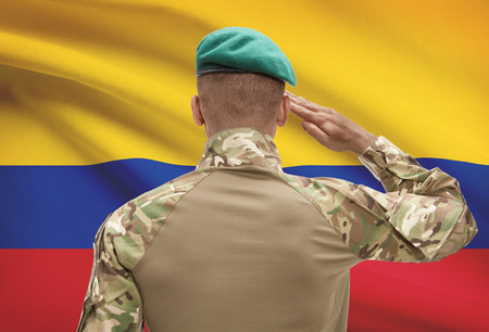 Dark-skinned soldier in hat facing national flag series - Colombia