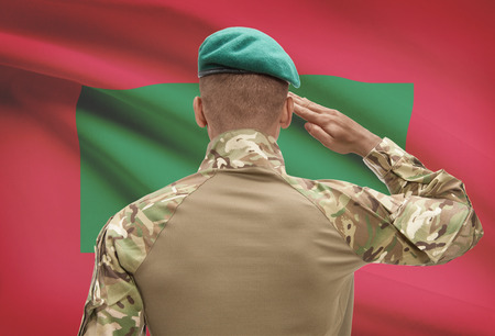 Dark-skinned soldier in hat facing national flag series - Maldives Stock Photo