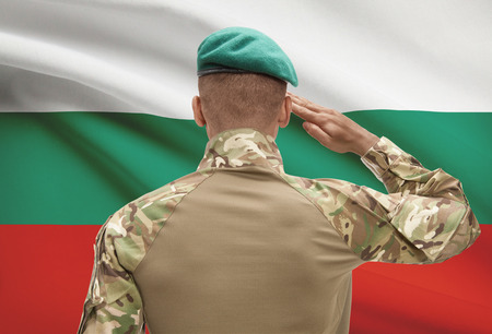 Dark-skinned soldier in hat facing national flag series - Bulgaria Stock Photo