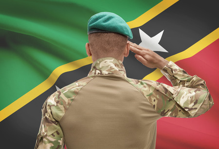 Dark-skinned soldier in hat facing national flag series - Saint Kitts and Nevis
