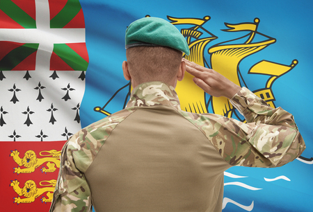 troop: Dark-skinned soldier in hat facing national flag series - Saint-Pierre and Miquelon Stock Photo