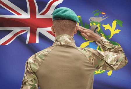 pitcairn: Dark-skinned soldier in hat facing national flag series - Pitcairn Island Stock Photo