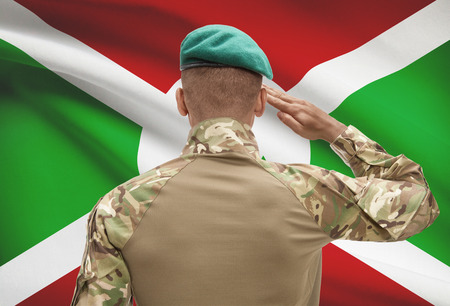 Dark-skinned soldier in hat facing national flag series - Burundi