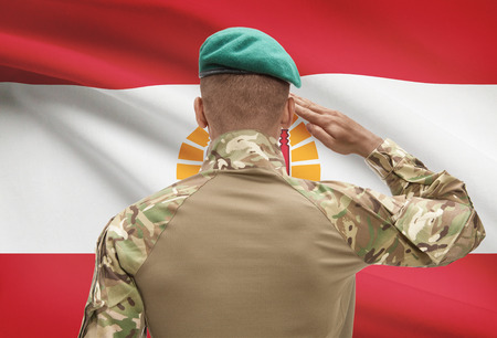 polynesia: Dark-skinned soldier in hat facing national flag series - French Polynesia Stock Photo