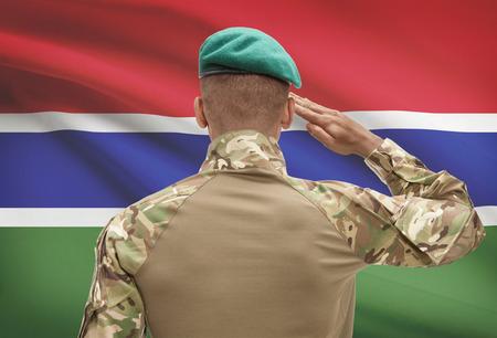 Dark-skinned soldier in hat facing national flag series - Gambia