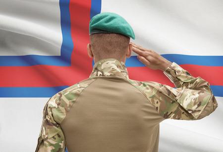 troop: Dark-skinned soldier in hat facing national flag series - Faroe Islands Stock Photo