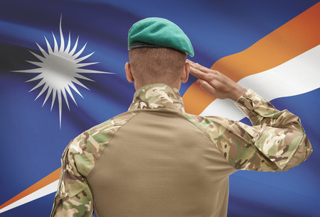 Dark-skinned soldier in hat facing national flag series - Marshall Islands Stock Photo
