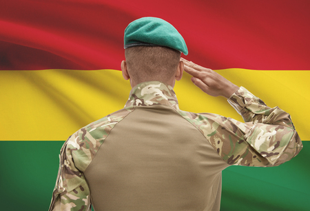 Dark-skinned soldier in hat facing national flag series - Bolivia Stock Photo
