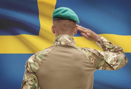 bandera de suecia: Dark-skinned soldier in hat facing national flag series - Sweden Foto de archivo