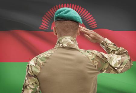 troop: Dark-skinned soldier in hat facing national flag series - Malawi