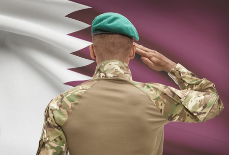 Dark-skinned soldier in hat facing national flag series - Qatar Stock Photo