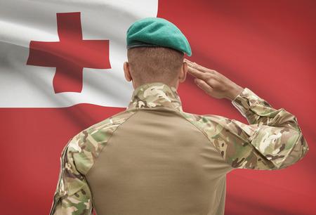 tonga: Dark-skinned soldier in hat facing national flag series - Tonga