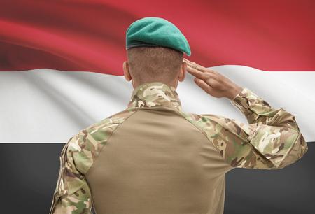 Dark-skinned soldier in hat facing national flag series - Yemen Stock Photo