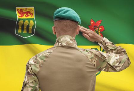 saskatchewan flag: Dark-skinned soldier in hat facing Canadian province flag series - Saskatchewan