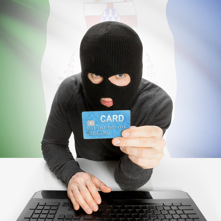 money risk: Hacker holding credit card and Canadian province flag - Yukon