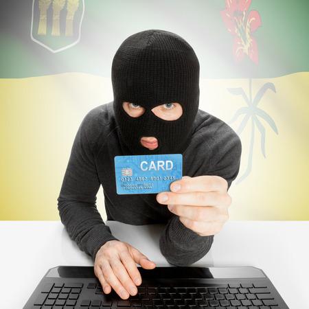 saskatchewan flag: Hacker holding credit card and Canadian province flag - Saskatchewan