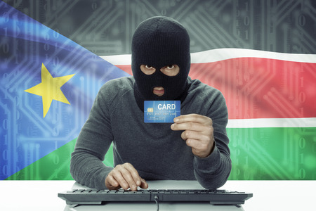 south sudan: Dark-skinned hacker with credit card and flag on background - South Sudan