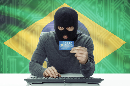 law of brazil: Dark-skinned hacker with credit card and flag on background - Brazil Stock Photo