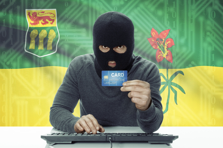 saskatchewan flag: Dark-skinned hacker with credit card and Canadian province flag on background - Saskatchewan Stock Photo