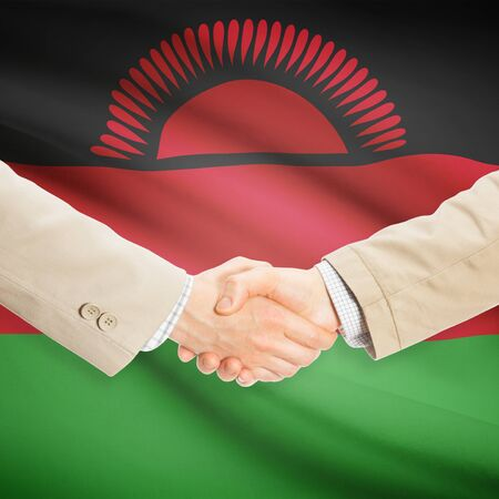 malawian flag: Businessmen shaking hands with flag on background - Malawi